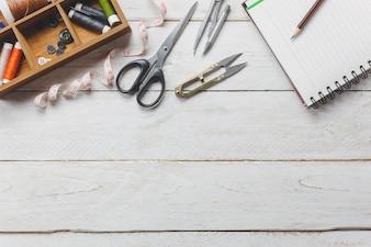 Los accesorios de la vista superior diseñan el concepto. Las herramientas del taladro están cortando las tijeras, los carretes del hilo, la cinta métrica, los botones y la ropa de costura. Cuaderno de texto de espacio libre sobre fondo de madera rústica.