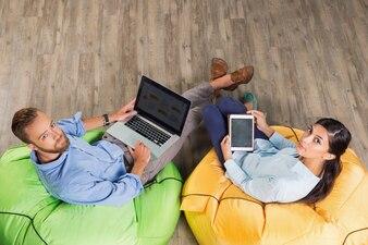 Los colegas masculinos y femeninos con el ordenador portátil y la tableta