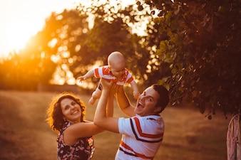 Los padres alegres sostienen a su pequeño hijo para arriba parado afu