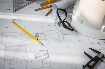 Los planes de construcción con casco y herramientas de dibujo blanco sobre bluepr