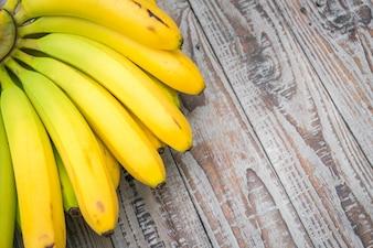 Los plátanos frescos en la mesa de madera.