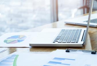 Lugar de trabajo con la computadora portátil abierta con el escritorio de madera moderno, cuaderno anguloso en la tabla en el interior casero, imagen filtrada, foco selectivo.
