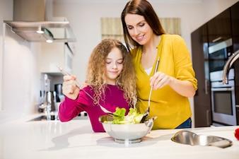 Madre ayudando a su hija en hacer la ensalada