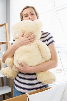Madre deprimida que sostiene el oso de peluche
