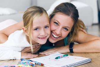 Madre e hija sonriendo sobre un escritorio