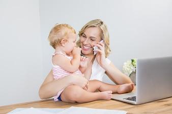 Madre que habla en el teléfono móvil mientras sostiene a su bebé