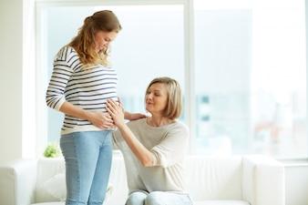 Madre tocando la barriga de su hija