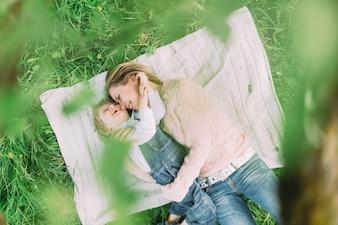 Madre tumbada con su hijo en un parque