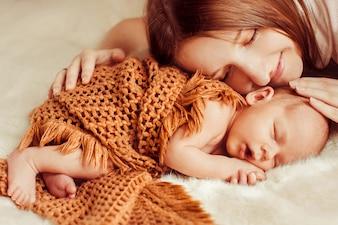 Madre tumbada encima de un bebé