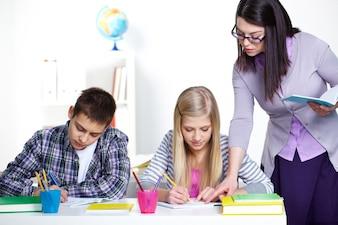 Maestra corrigiendo errores en el cuaderno de la alumna