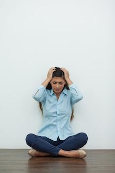Malestar mujer que se sienta en el suelo y la cabeza Clutching