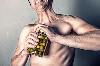 El hombre tratando de abrir un frasco de encurtidos