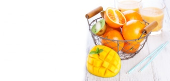 Mango fresco junto a una cesta con naranjas