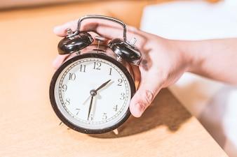 Mano cogiendo el reloj despertador de cerca