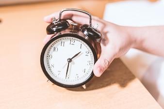 Mano cogiendo el reloj despertador