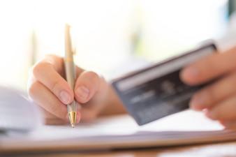 Mano con la pluma y la tarjeta de crédito sobre el formulario de aplicación.