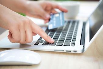 Mano con una tarjeta de crédito y un portátil