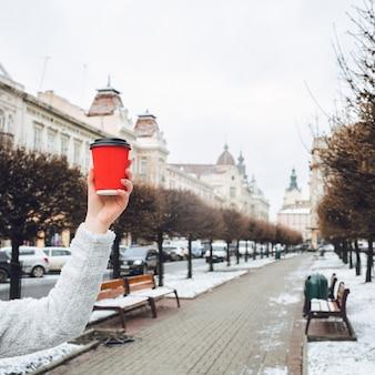 Mano de la mujer sostiene la taza de papel roja antes del callejón en el casco antiguo de la ciudad