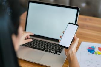 Mano de mujer de negocios con gráficos financieros y el teléfono móvil sobre la computadora portátil en la tabla.