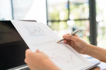 Mano de mujer de negocios con gráficos financieros y portátil sobre la mesa