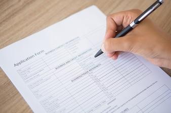 Mano que completa el formulario de solicitud