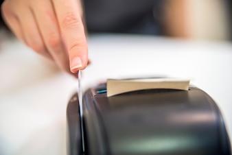 Mano roba crédito rojo a través de terminal de pago. Tarjeta de débito en la terminal. Máquina de lector de tarjetas de crédito sobre fondo blanco