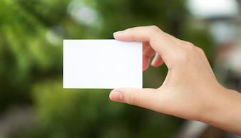 Mano sujetando un papel blanco con el fondo desenfocado