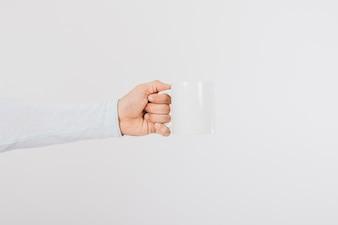 Mano sujetando una taza de café de perfil