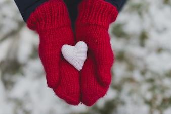 Manos con guantes sujetando un corazón blanco