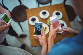 Manos con móviles y cafés de fondo