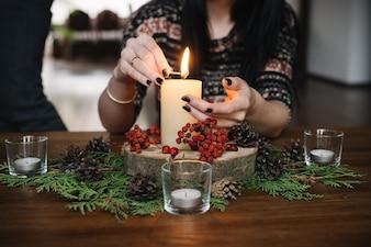 Manos de mujer encendiendo una vela