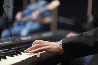 Manos de pianista con guitarrista en el fondo