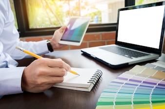 Manos del diseñador gráfico moderno del inconformista masculino en la oficina que trabaja con las muestras del color. Hombre en el lugar de trabajo elegir muestras de color, de cerca. Concepto de personas creativas.