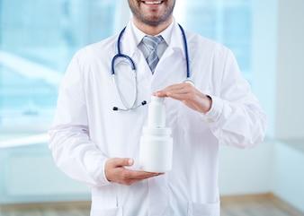 Manos en primer plano del doctor sosteniendo dos envases