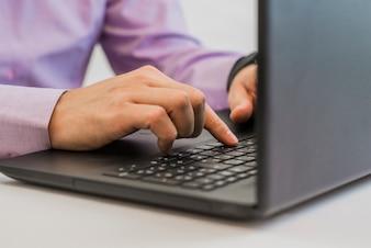 Manos escribiendo en un portátil