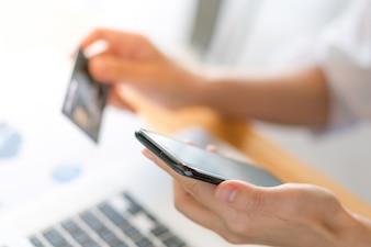 Manos que sostienen una tarjeta de crédito usando la computadora portátil y el teléfono móvil para las compras en línea
