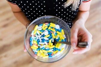 Manos sosteniendo una variedad de medicamentos farmacéuticos píldoras y cápsulas en un recipiente.