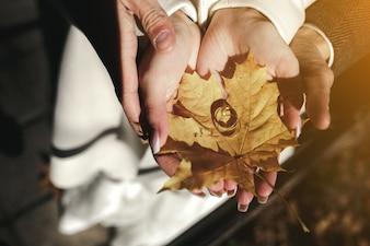 Manos sujetando una hoja seca con dos anillos de boda