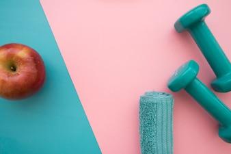 Manzana, toalla y pesas sobre fondo azul y rosa