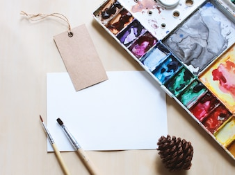 Maqueta de espacio de trabajo de artista con pincel y pintura en tarjeta en blanco