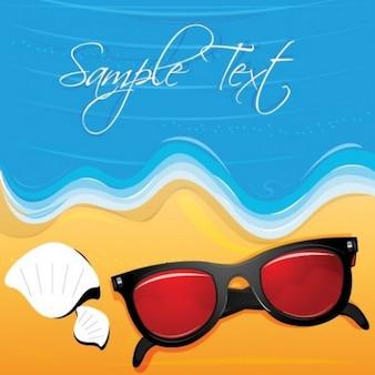 Mar y la playa de arena con conchas y gafas de sol