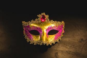 Máscara veneciana dorada sobre una mesa de madera