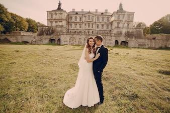 Matrimonio riendo con edificio antiguo de fondo