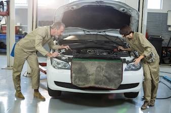 Mecánica que examinan motor de un coche