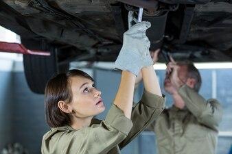 Mecánica que examinan un coche