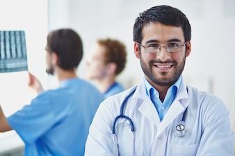 Médico con compañeros de trabajo de fondo