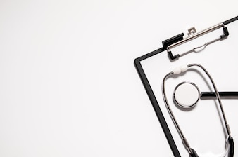 Médico estetoscopio o fonendoscopio aislado sobre fondo blanco recortar. Estetoscopio y portapapeles con la hoja blanca en blanco de papel y copia espacio. Concepto médico