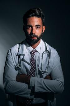 Médico posando en la oscuridad