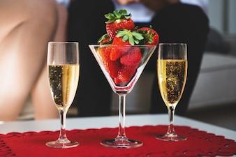 Mesa con una copa con fresas y dos copas de champán