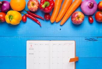 Mesa con verduras y una agenda